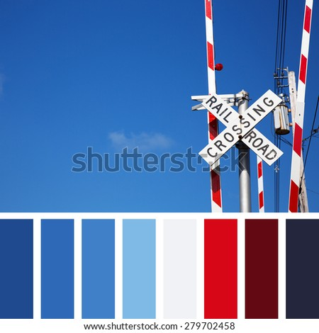 Railroad crossing sign against blue sky background. In a colour palette with complimentary colour swatches. - stock photo