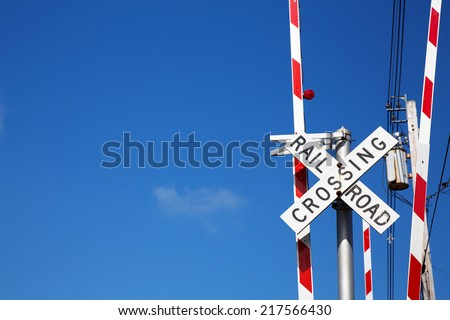 Railroad crossing sign against blue sky background, with space for your text. - stock photo