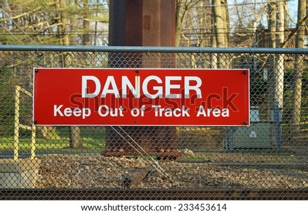 Railroad Crossing Sign. Red danger sign at a railroad station warns pedestrians to stay off the tracks.  - stock photo