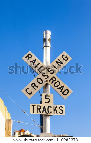 railroad crossing sign with blue sky - stock photo
