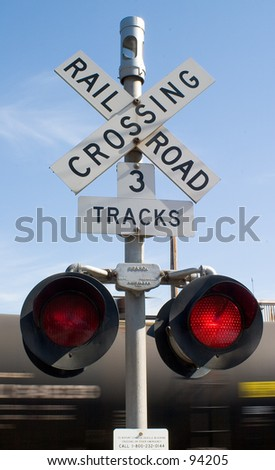 Railroad crossing sign, with train in motion.