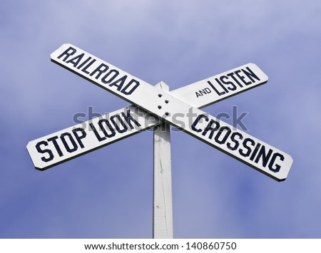 Railroad crossing sign with warning to stop, look, and listen - stock photo