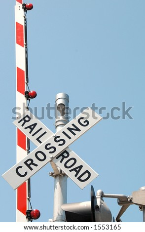 Railroad crossing signal against a blue sky.