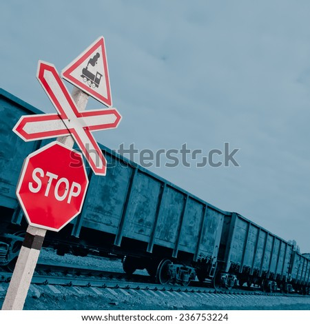 railroad crossing signs and composition of railway wagons - stock photo