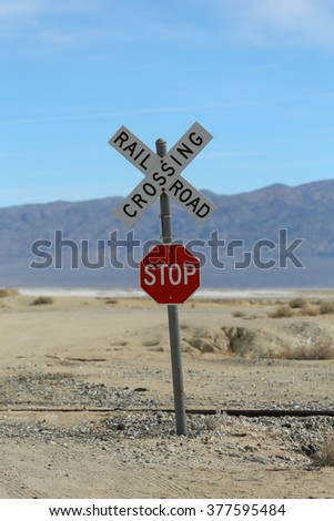 Railroad Crossing Stop Sign / A railroad crossing sign with a stop sign underneath in the desert with mountains in the background on a semi cloudy and clear day.