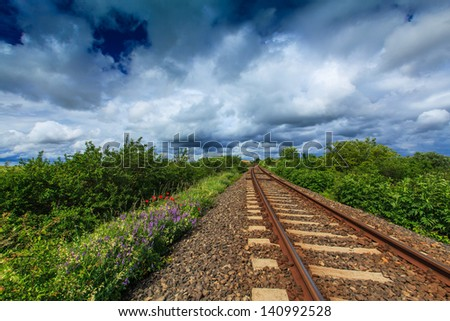 Railroad in rural area, with storm clouds on the horizon