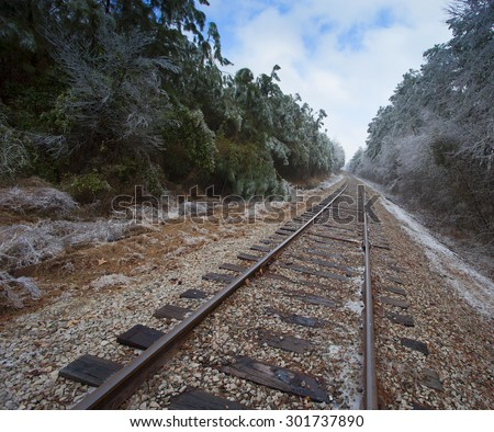 Railroad line that is winding through an ice covered forest - stock photo