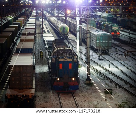 Railroad night scene with lights and cargo trains - stock photo