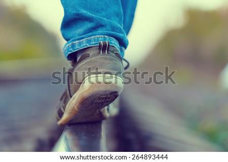 railroad rails feet sneakers jeans - stock photo