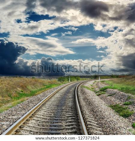 railroad to horizon and dramatic sky - stock photo