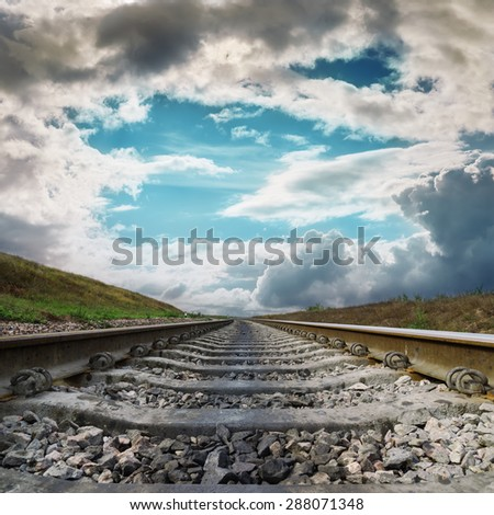 railroad to horizon in dramatic clouds - stock photo