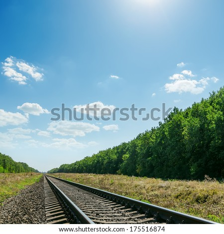 railroad to horizon in green landscape and blue sky with sun over it - stock photo