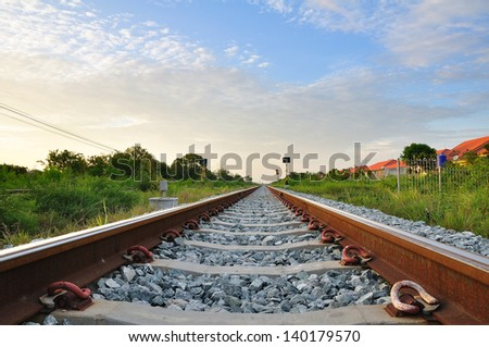 railroad to horizon under cloudy sky - stock photo