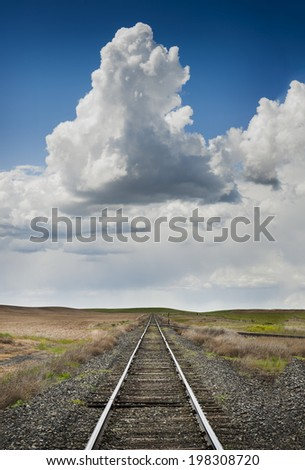 Railroad to Nowhere. Railroad tracks lead straight to the horizon in this scene in the Palouse area of eastern Washington state.  - stock photo