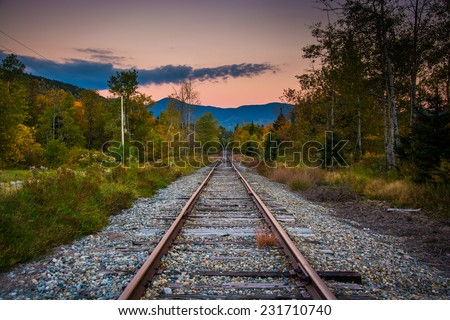 Railroad track and distant mountains at sunset seen in White Mountain National Forest, New Hampshire. - stock photo