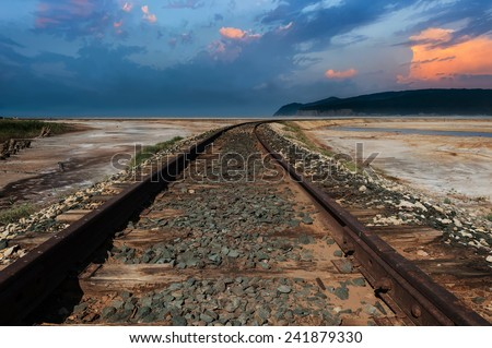 Railroad track in the desert, under dramatic sky - stock photo