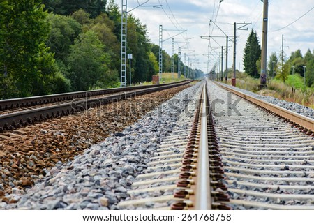 Railroad track vanishing into the distance, summer time - stock photo