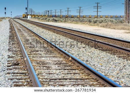 Railroad tracks and train with power lines - stock photo