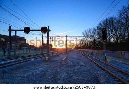 Railroad tracks at a station at a winter sunrise. - stock photo