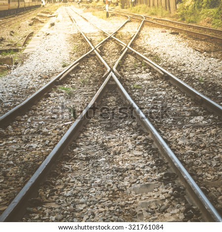 Railroad tracks crossing of a Public Thai Train Railway , process in vintage style - stock photo