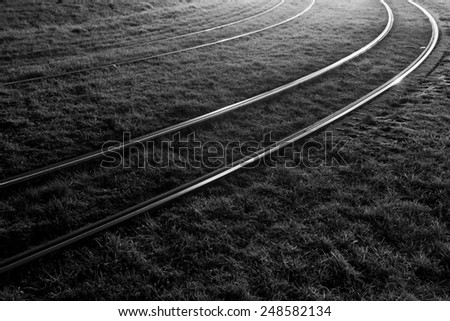 railroad tracks curve at night  - stock photo
