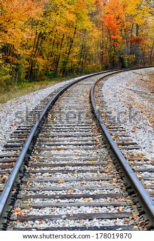 Railroad tracks curve through a landscape full of colorful fall foliage. - stock photo