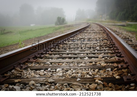 Railroad tracks in fog - stock photo