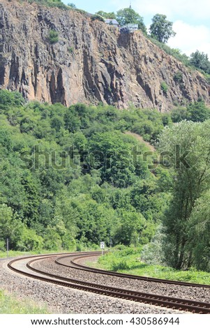 Railroad tracks lead through a natural landscape
