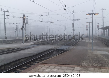Railroad tracks leading into thick mysterious fog on a cold and wet winter day - stock photo