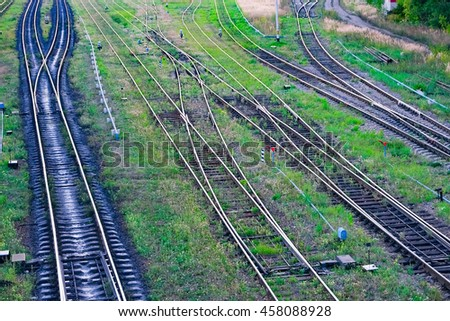 Railroad tracks on gravel at train station - stock photo