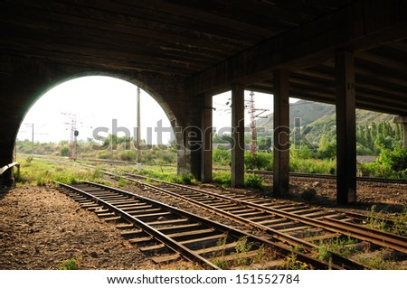 Railroad tracks passing under the arched bridge  - stock photo