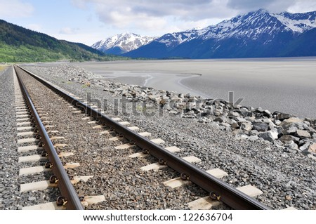 Railroad tracks running through Alaskan landscape - stock photo