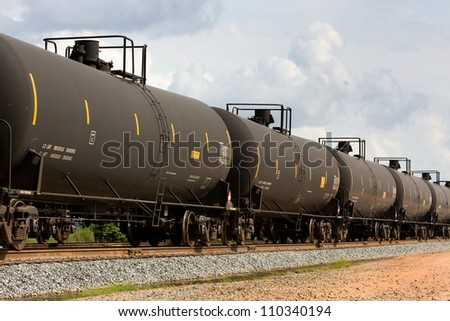 Railroad train of tanker cars transporting crude oil on the tracks.