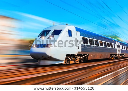 Railroad travel and railway tourism transportation industrial concept: scenic summer view of modern high speed passenger commuter train on tracks at the station platform with motion blur effect - stock photo