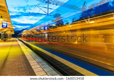 Railroad travel and transportation industry business concept: summer evening view of high speed commuter passenger train departing from railway station platform with motion blur effect - stock photo