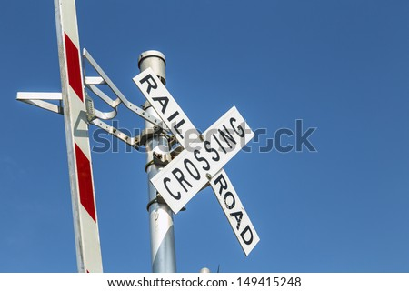 Railroad warning crossing sign under clear blue sky - stock photo