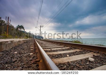 railroad with dramatic sky near ocean - stock photo