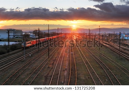 Railroad with train at sunset and many lines