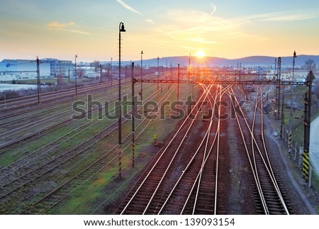 Railroad with train at sunset and many lines - stock photo