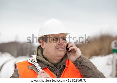 Railroad worker talking on the cell phone - stock photo