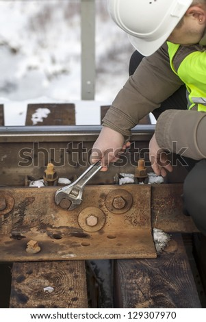 Railroad worker with wrench fix the nut on the bridge - stock photo