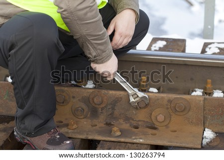 Railroad worker with wrench on the railway bridge fix the nut - stock photo