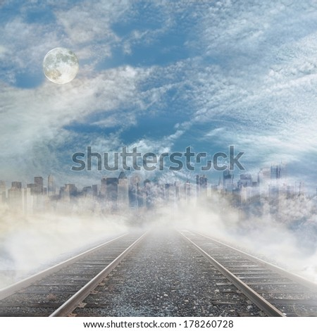 Rails to foggy city skyline with cloudy sky and full moon. - stock photo
