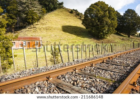 Railway and old cottage, Whangamomona. a traditionally deserted rural cottage illuminated by warm sunshine with green field and pasture on the hillside behind, rusty railway line in foreground. - stock photo