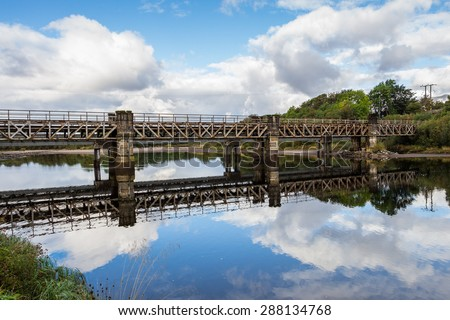 Railway beam bridge crossing River Lochy on stone piers beside Old Inverlochy Castle in Fort William, Highland, Scotland, UK. The cloud scape and blue sky reflects like a mirror on the quiet waters. - stock photo