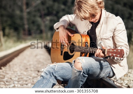 Railway blues. Young man playing on guitar on the railway - stock photo