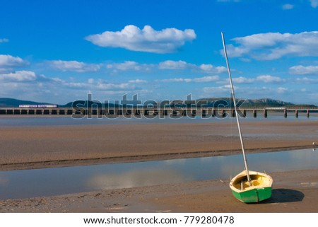 Railway Bridge at Arnside Bay. A small fishing boat on the shore at Arnside in the English Lake District, Great Britain