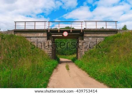 Railway bridge over a rural gravel road - stock photo