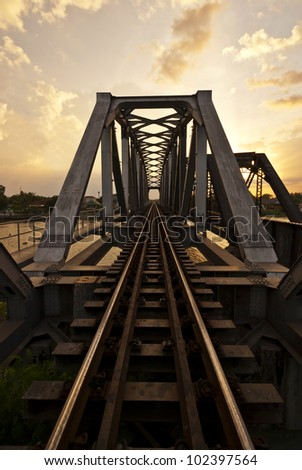 Railway Bridge over the River Nakornchaisri at Sunset - stock photo