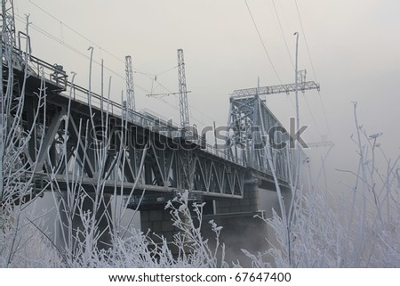 Railway bridge through the river in the winter